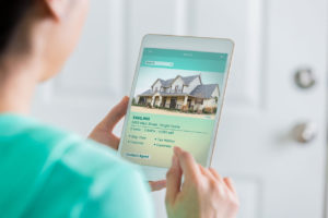 Woman on Tablet Looking at Harlan Ranch Property Costs