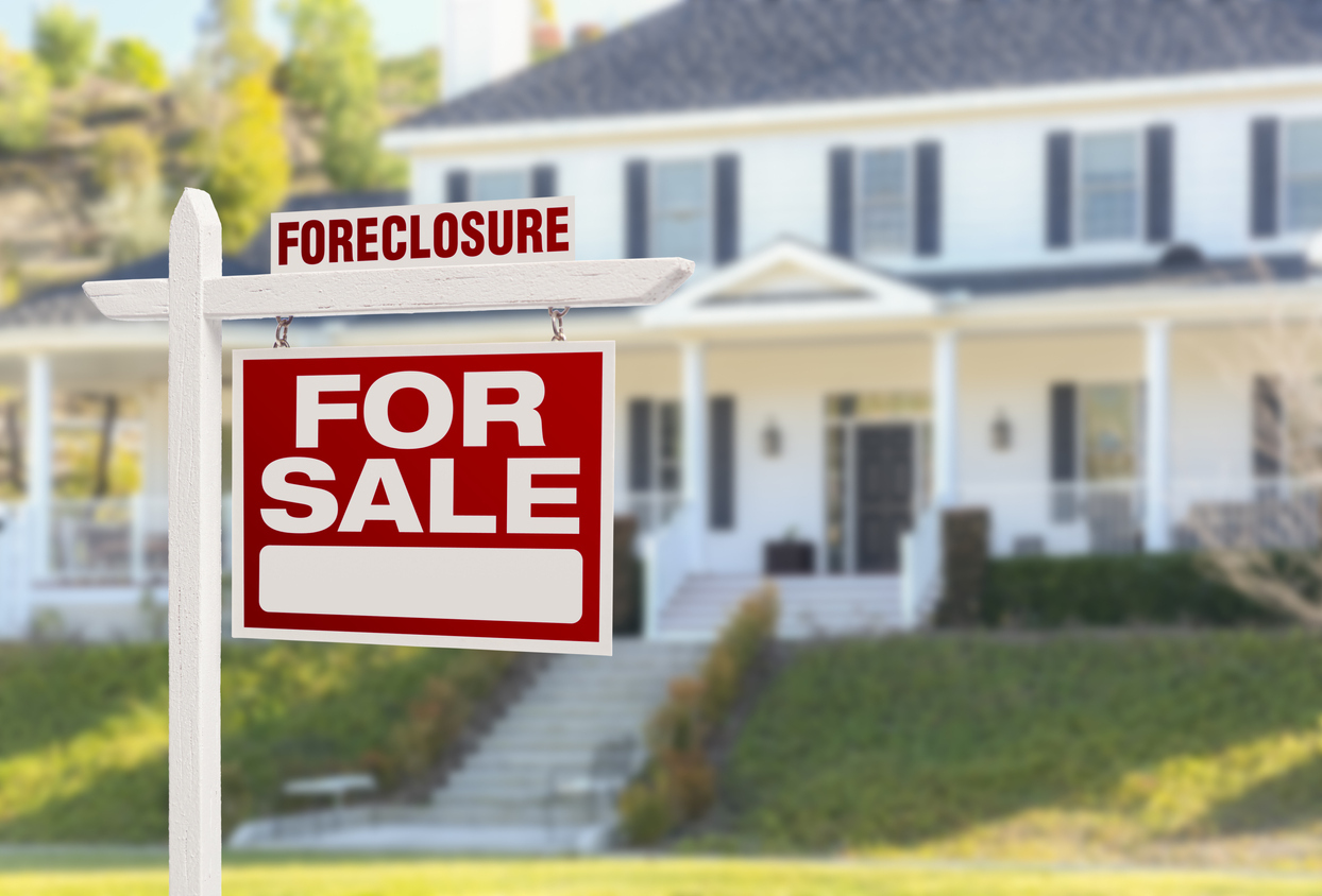 White Melba House with Foreclosure Sign in Yard