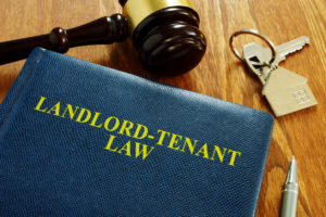 Landlord Tenant Law Book on a Desk with Gavel and House Keys