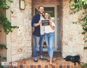 """Portrait of a young couple holding a chalkboard with """"our first home"""" written on it"""