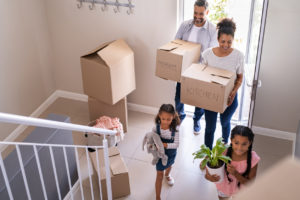 family with two children carrying boxes and plant in new home on moving day
