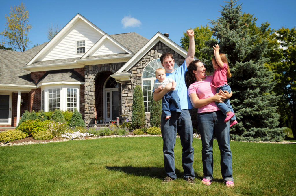 A young family celebrating in front of a new home.