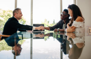 Male real estate broker shaking hands with new property owners while sitting across a table. Property seller congratulating couple on making deal on new property investment.