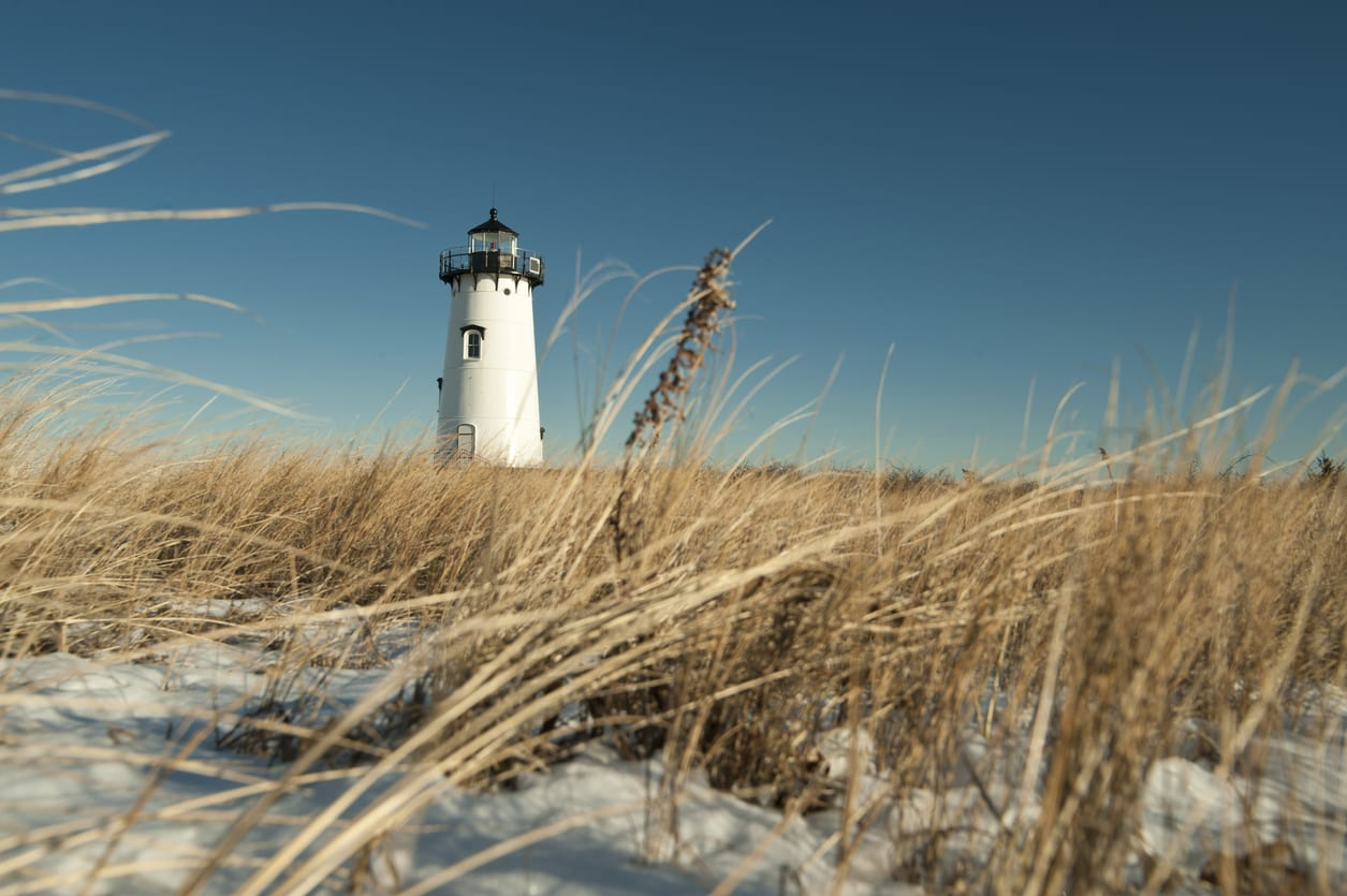 Cape Cod lighthouse with dried grass and snow in the foreground