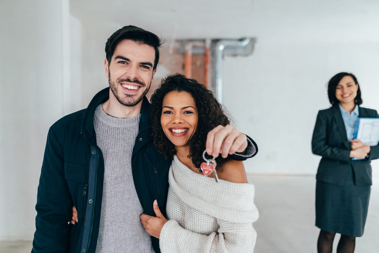 Couple moving into new home with property manager in background