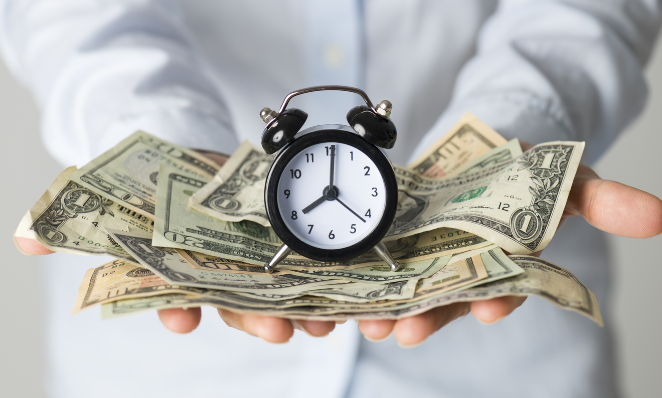 Woman holding paper currency and alarm clock