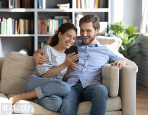 Couple in Lubbock Apartment Smiling at a Smartphone