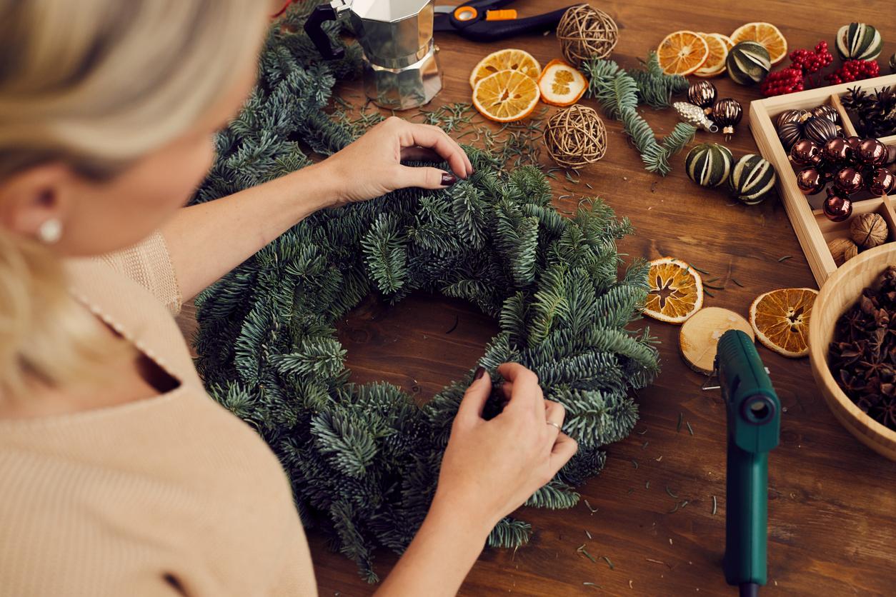 Woman Crafting a Winter Wreath with Hot Glue Gun