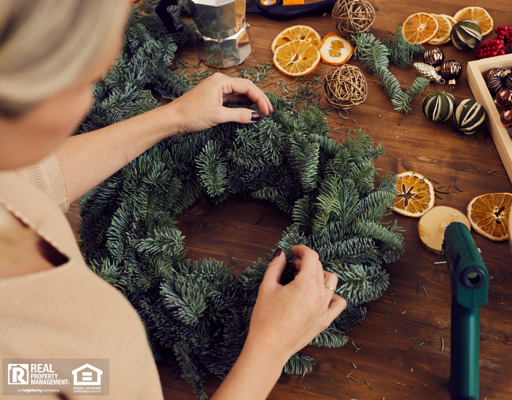 Woman Crafting a Winter Wreath with Hot Glue Gun