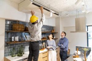 HVAC Repairman Servicing AC Unit in Kitchen