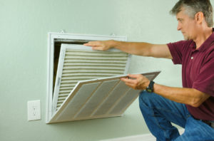 China Spring Homeowner Replacing Air Filter on Their Air Conditioner