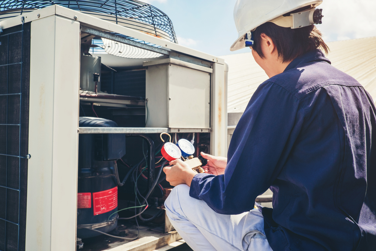 Technician Checking Air Conditioner at a Rental Home in Caldwell