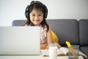 Child Learning Online with Black Headphones On