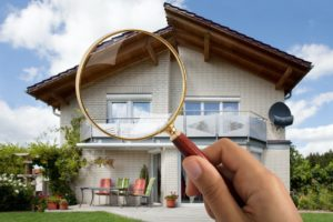 Hand Holding Magnifying Glass Over Rental Property