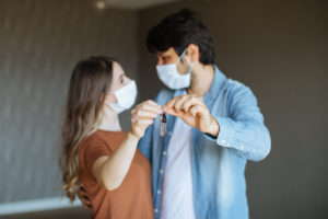Couple with Face Masks Holding Keys to Their New Carmel Apartment
