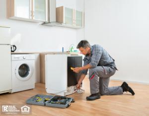 Greenwood Property Manager Doing Maintenance on Appliances