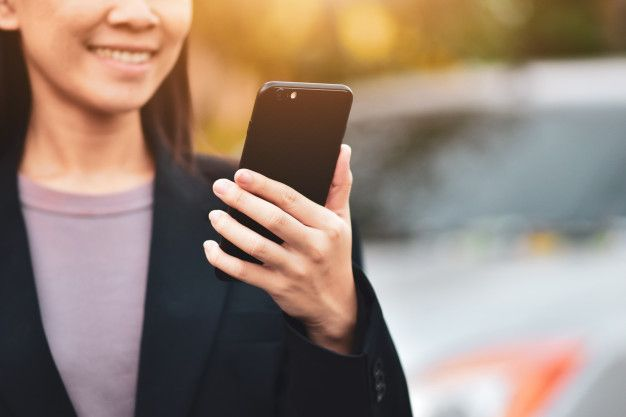 Woman holding iPhone looking for top real estate investment apps