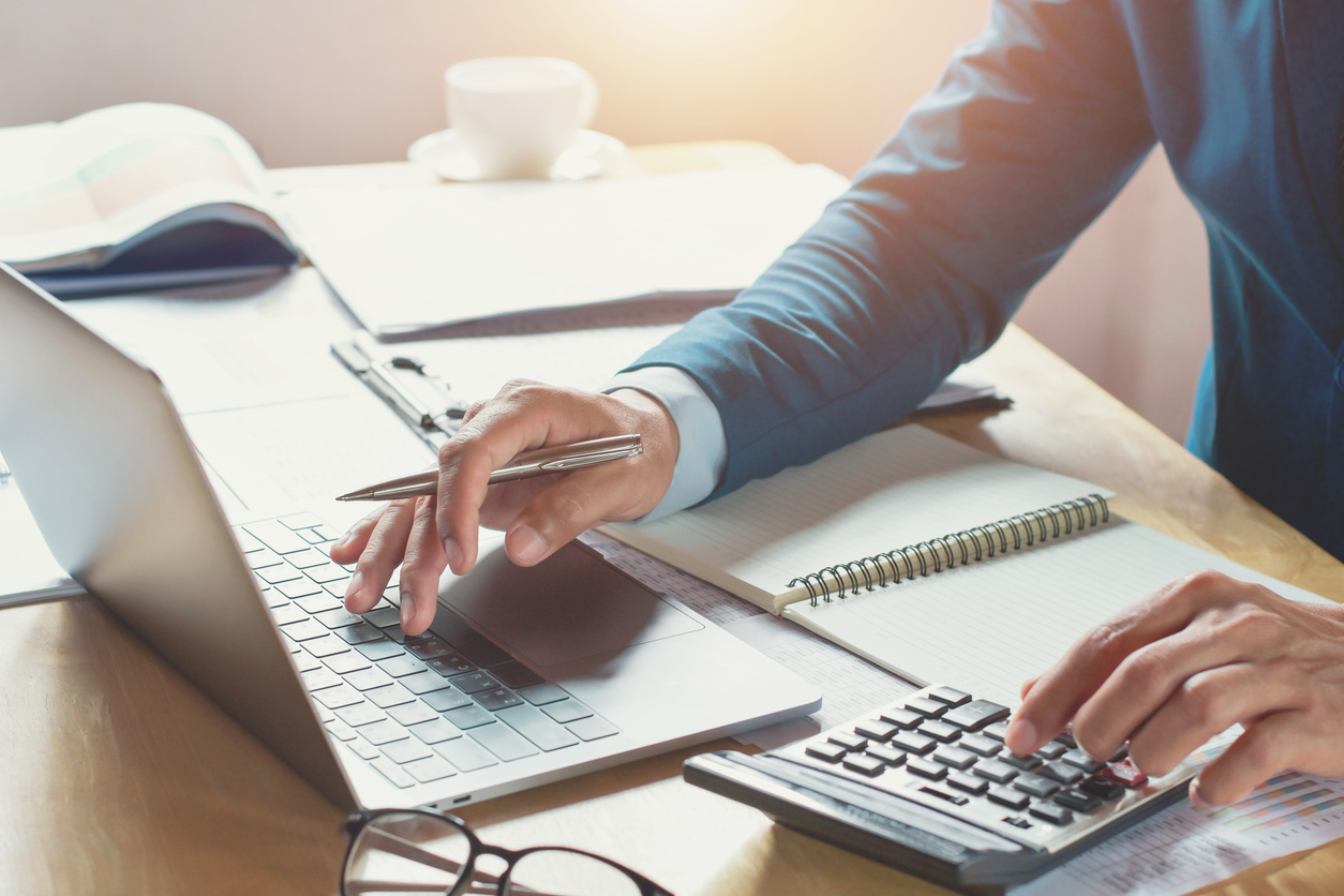 businessman working in office with using calculator and laptop. concept finance and accounting