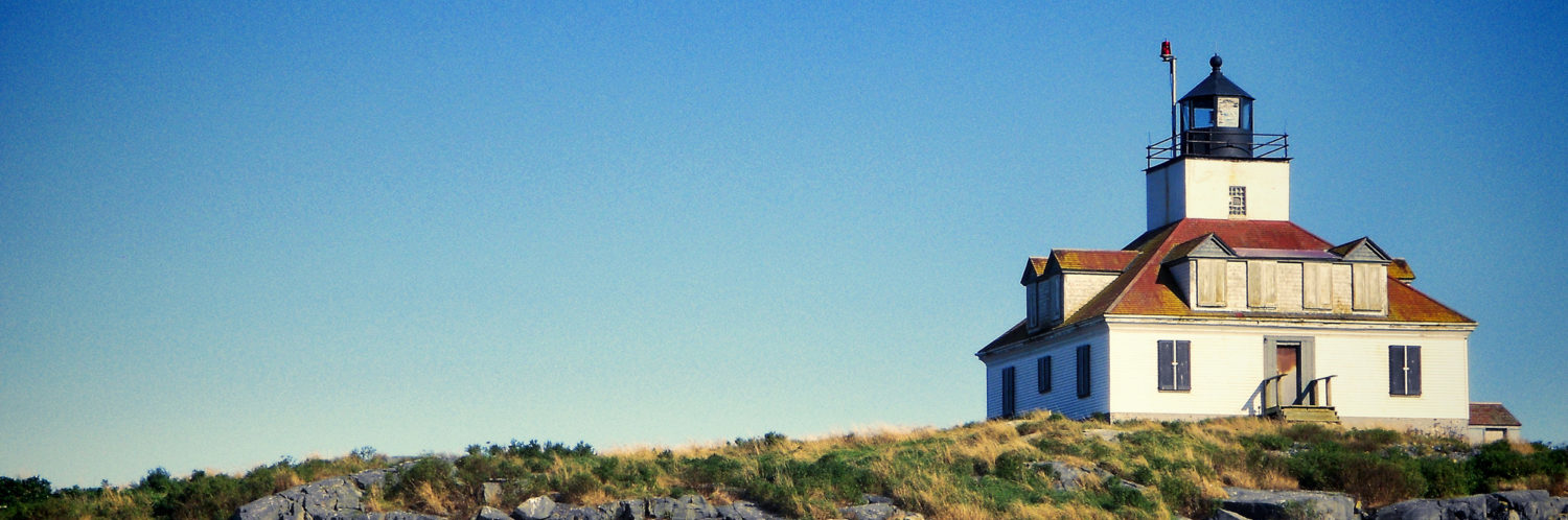 Historic New England Island lighthouse on a beautiful day, with clear blue skies.