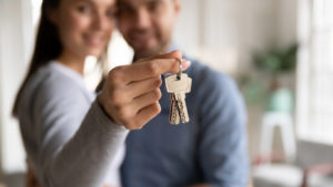 Happy Couple with Woman Holding Keys