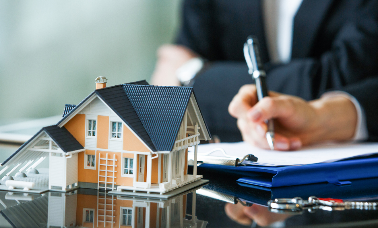 Filling Out Insurance Paperwork with a Model House in the Forefront