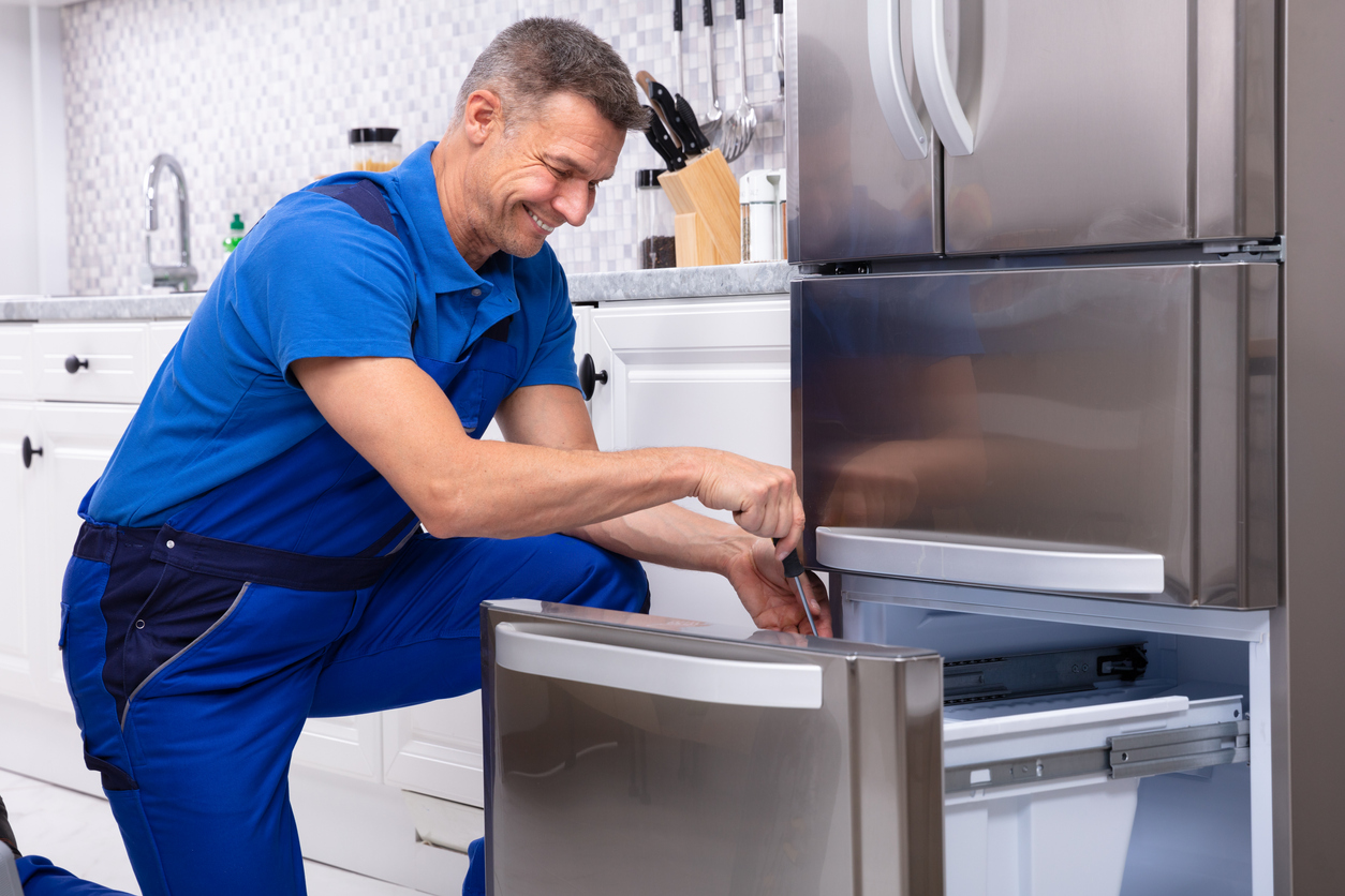 Serviceman Repairing Refrigerator