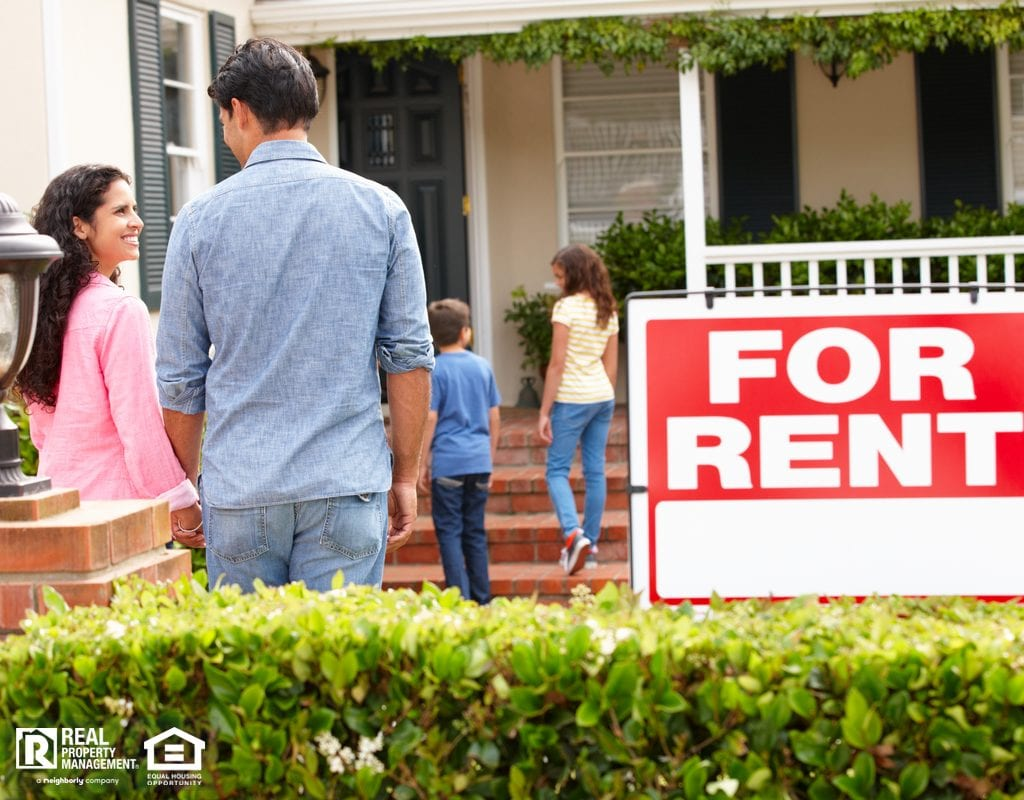 Happy Family Walking into Suburban Home with For Rent Sign in Yard