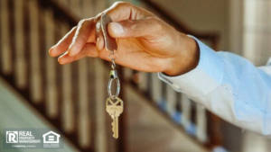 Person holding the keys to their new real estate investment
