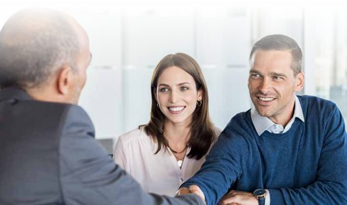 Couple Shaking Hands with a Business Man
