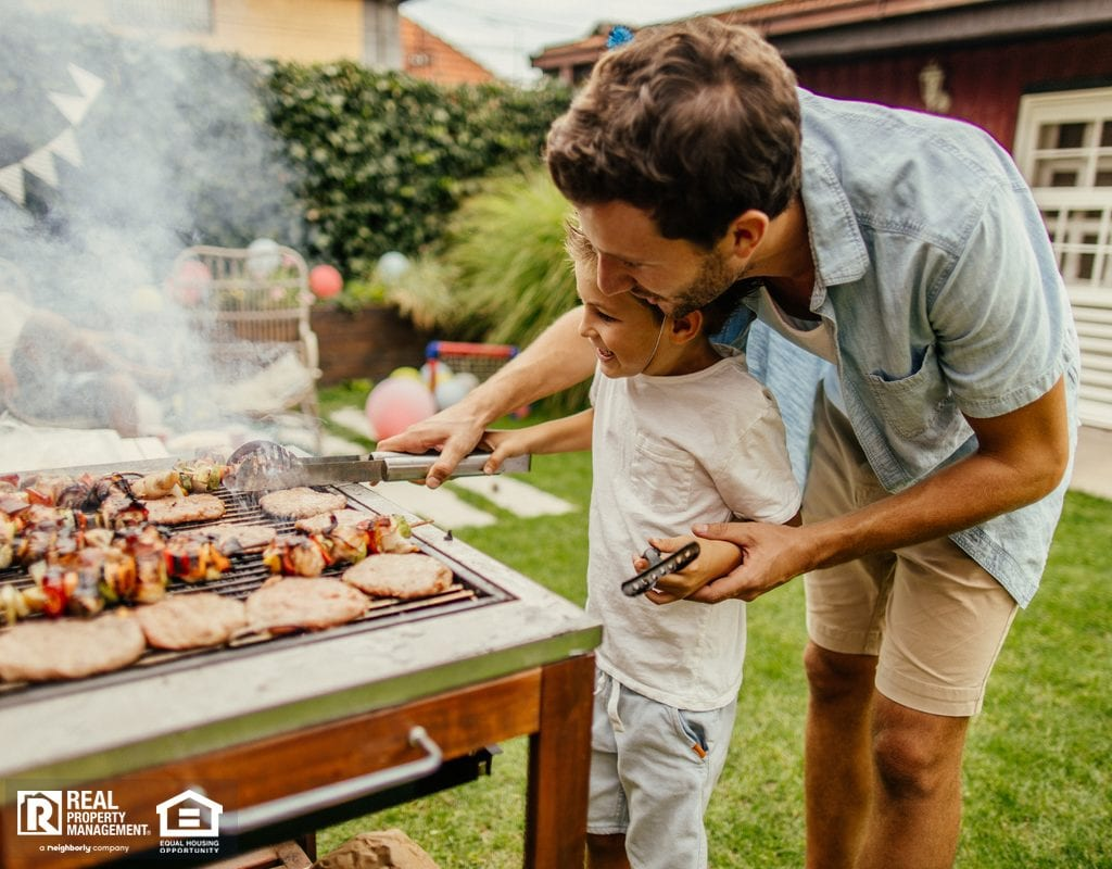 Father and Son Grilling in Yard of Cypress Rental Property