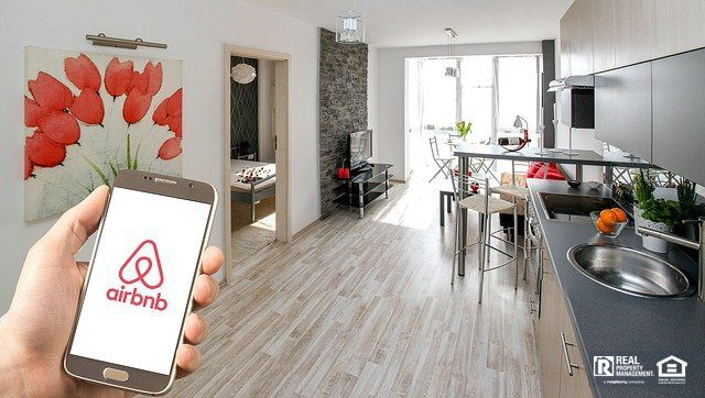 Person holding mobile phone with airbnb logo in front of living room
