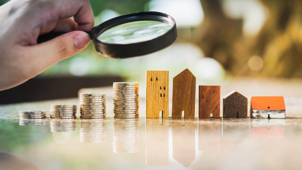 Hand holding magnifying glass and looking at house model with row of coin money