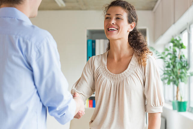 Young businesswoman shaking hands with male representative in office
