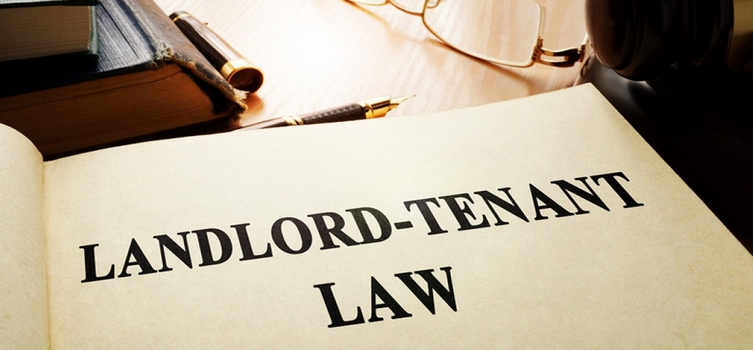 Open book of Landlord Tenant Law on a desk with pens