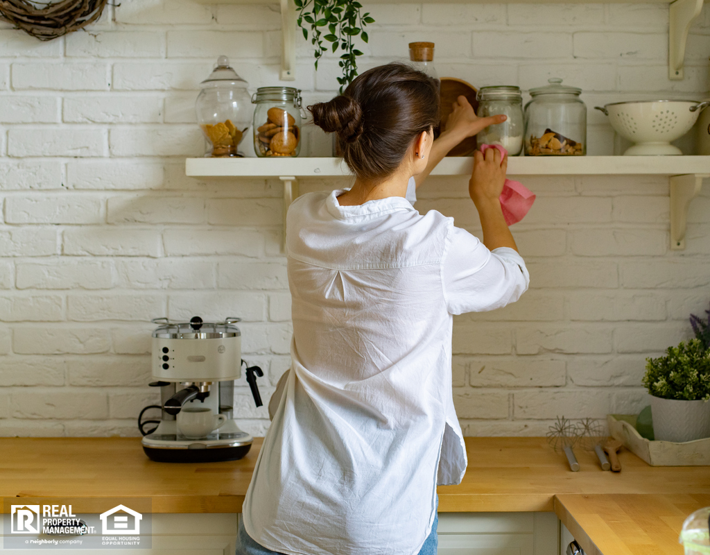 Woman Dusting Kitchen Shelves with a Microfiber Duster