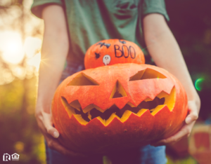 Westchester Resident Holding a Stack of a Decorated Pumpkin and a Jack-o-Lantern