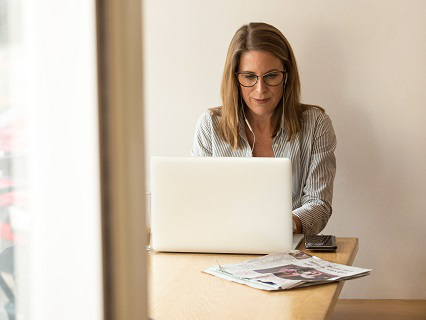 A Woman Typing on Her Laptop at the Kitchen Table