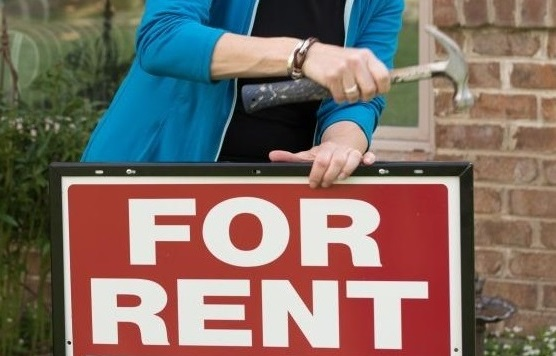 """Someone placing a """"For Rent"""" sign in front of a Milwaukee rental property"""