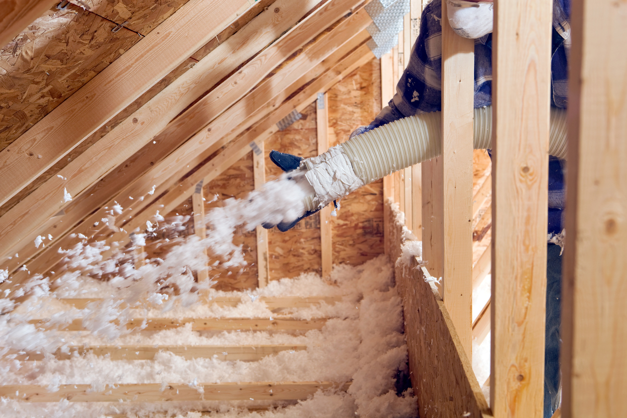 Spraying Blow-In Fiberglass Insulation Between the Attic Trusses of Your Milwaukee Rental Home