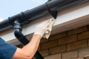 Man cleaning and maintaining plastic gutters