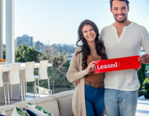 Young couple holding a leased rental sign in a luxury home