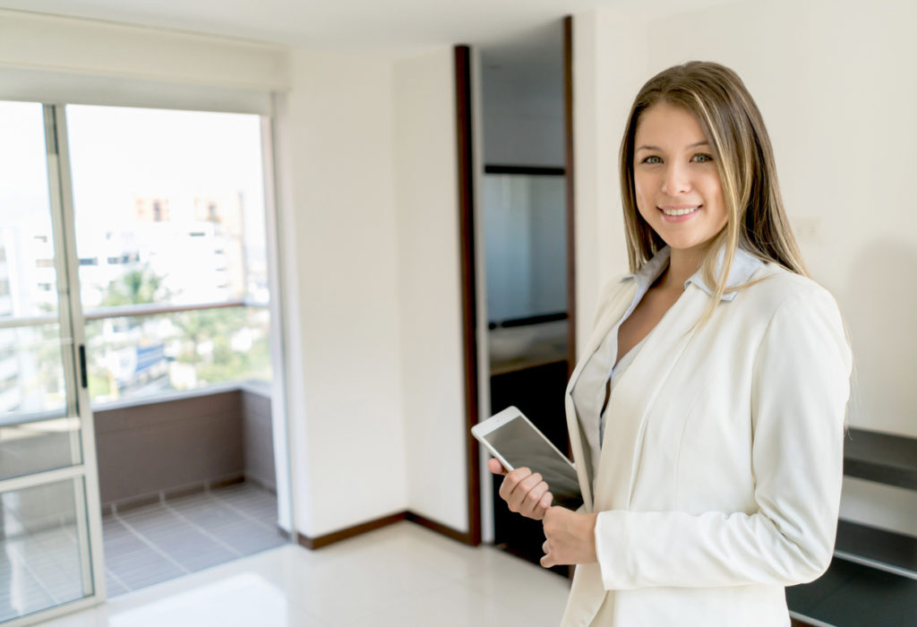 Confident latin american real estate agent at a property looking at camera smiling