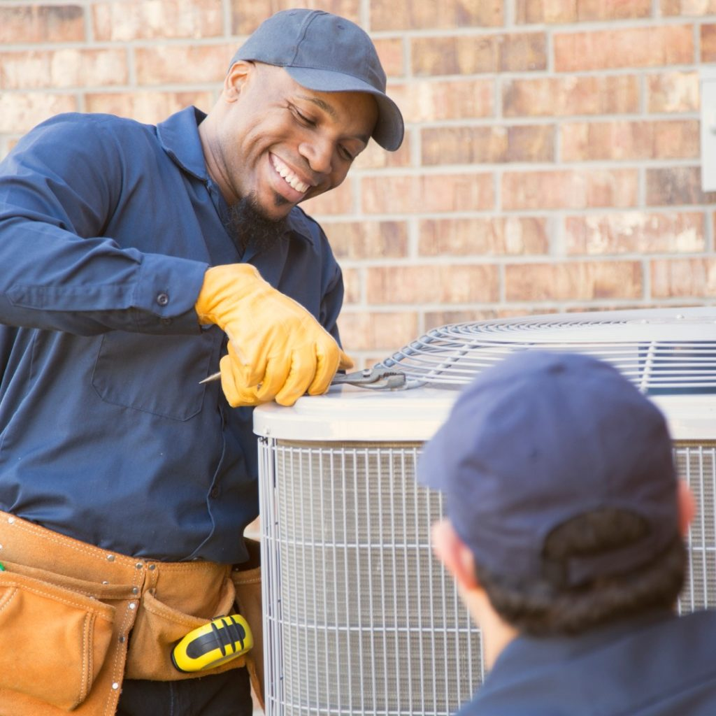 multiethnic-team-of-blue-collar-air-conditioner-repairmen-at-work-