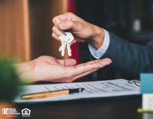 Agent Handing Property Investor Keys After Purchase