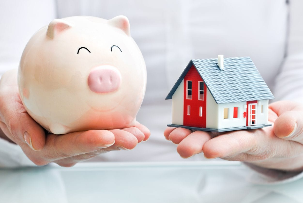 Hands holding piggy-bank and house model