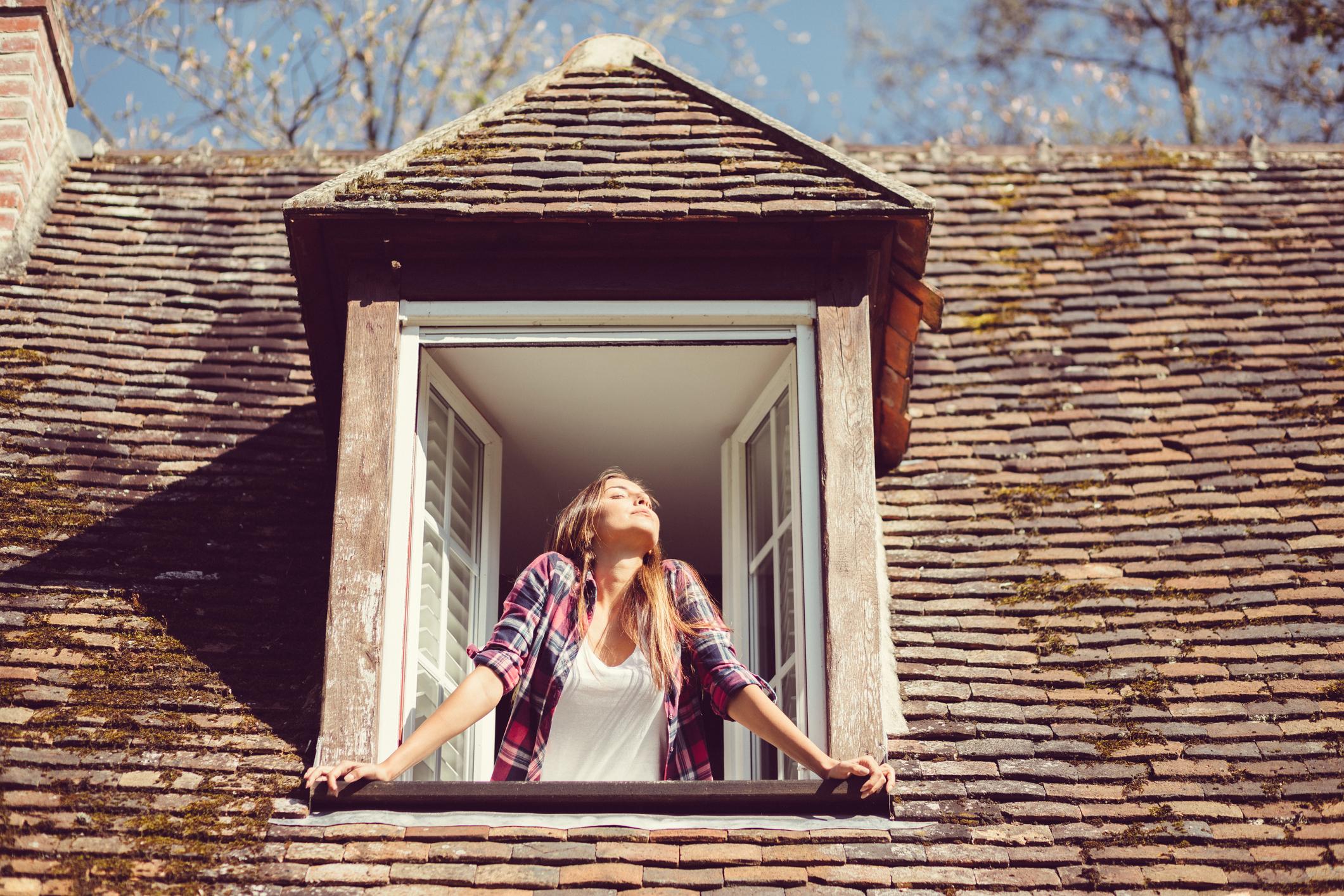 Woman Enjoying the Sunshine from a 2nd Story Window