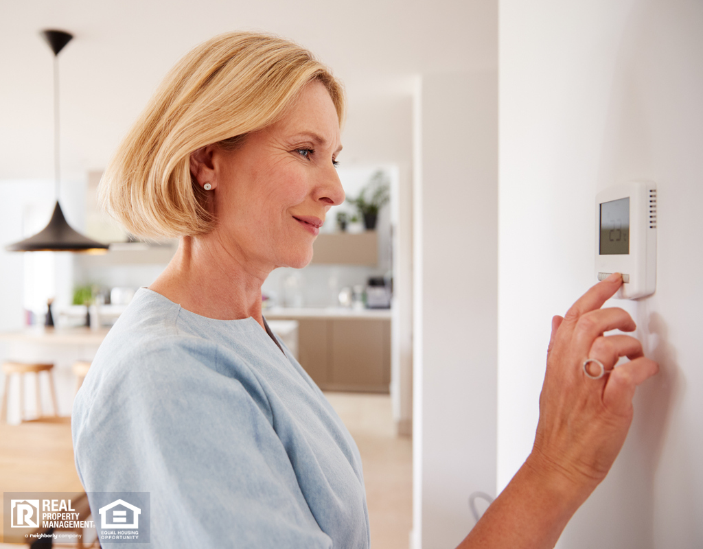 Older Woman Adjusting the Thermostat in Her Home