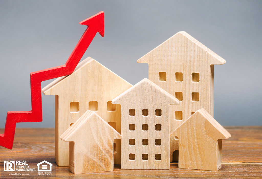 Miniature wooden houses and red arrow showing the concept of rental and mortgage rate increases.