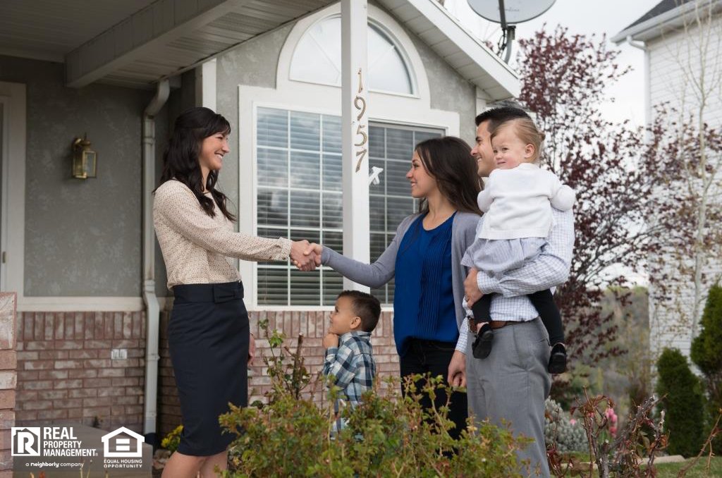 Leasing Agent Meeting with a Family Outside a Home