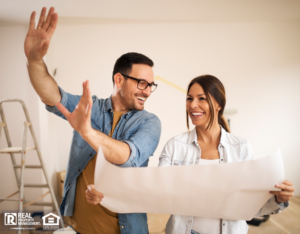 Young couple standing in their apartment while woman holding blueprint and man showing her new ideas.